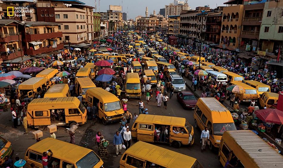 في نهاية يوم العمل، تكتظ سوق إديوموتا في جزيرة لاغوس بحافلات صغيرة، تنقل العمال العائدين إلى منازلهم في البر الرئيس، حيث يعيش معظم سكان لاغوس.