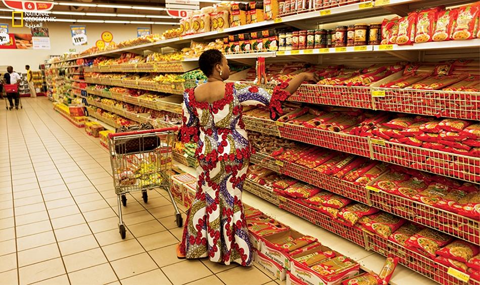 """تجوب إحدى المتسوقات أروقة البقالة بمتجر """"شوبرايت"""" الذي يقع مقره الأم في جنوب إفريقيا. يوجد هذا المحل التجاري داخل مركز التسوق """"آيكيجا سيتي مول"""" الذي فُتح قبل ثلاث سنوات."""