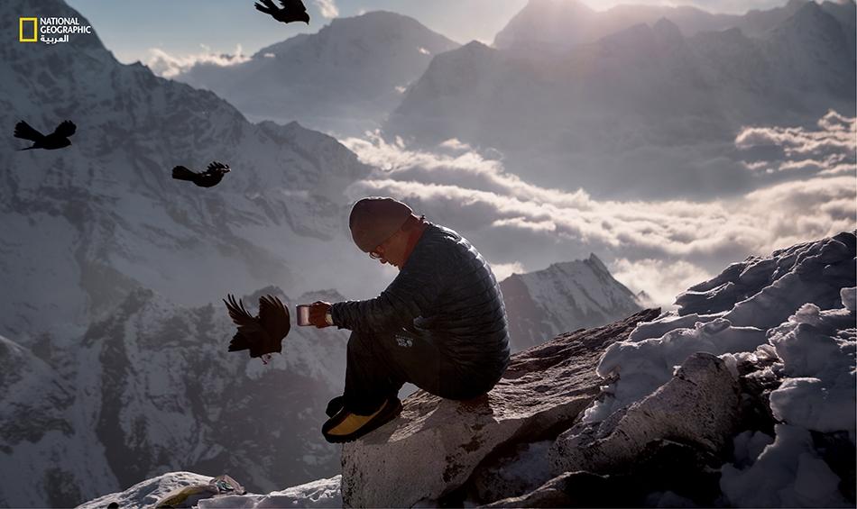 """ينتمي """"لاكبا"""" إلى قومية الشيربا، ويعمل دليلاً جبلياً ويمتلك شركةً لتنظيم بعثات التسلّق؛ وهو يجلس هنا في لحظة تأمل بين القمم القريبة من جبل إيفرست ليحتسي كوباً من الشاي على مرأى من الطيور. التُقطت هذه الصورة في عام 2013، أي قبل سنة واحدة على أكبر كارثة..."""