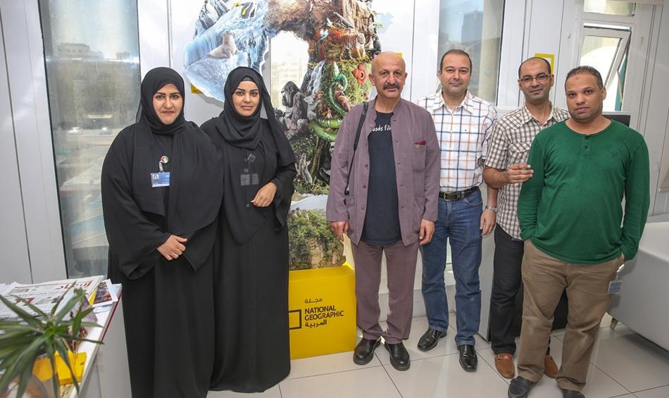 المصور العالمي رضا يتوسط فريق عمل مجلة ناشيونال جيوغرافيك العربية