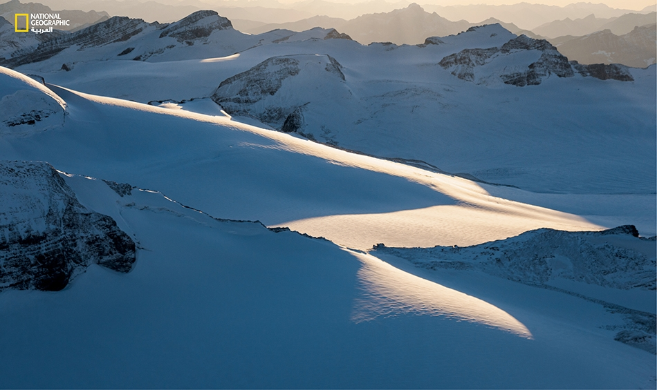 """أشعة شمس الأصيل ترسم شرائح على """"حقل وابتا الجليدي""""، وهو سلسلة من الأنهار الجليدية على امتداد """"الفاصل القاري""""."""