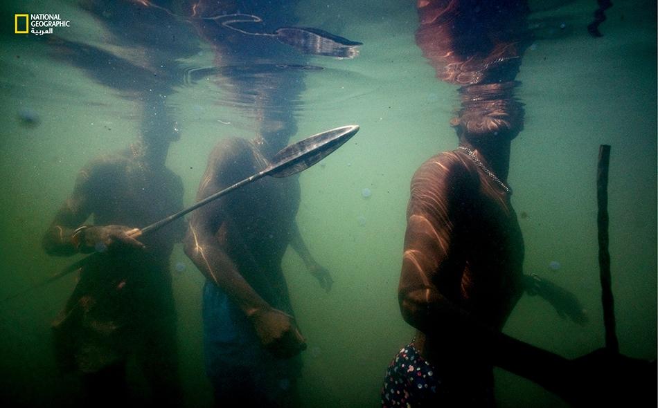"""رجال من قبيلة """"إلمولو"""" يتعقبون الأسماك بطريقة تقليدية على طول الضفة الشرقية لبحيرة """"توركانا""""، سلاحهم رماح.. وصبر."""