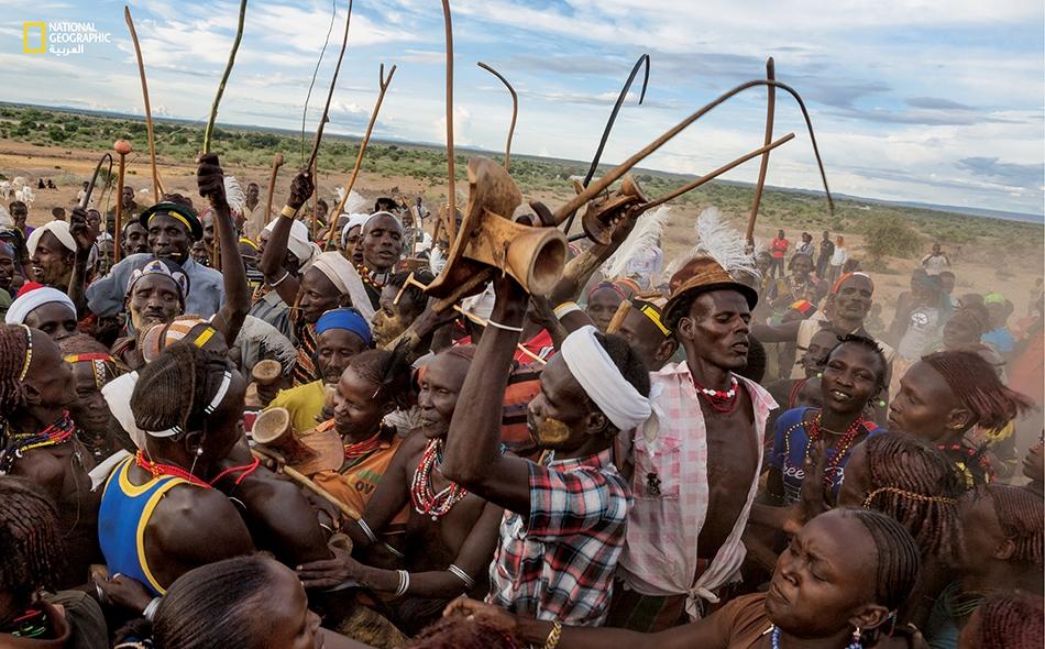 """يُلوِّح رجال من قبيلة """"داساناش"""" بسياطهم وعصيهم ومقاعدهم التقليدية وقد تزين بعضهم بريش النعام. يرقص هؤلاء وسط جمهرة من النساء المرشَّحات للزواج في حفل تزاوج بقرية """"إليريت""""."""