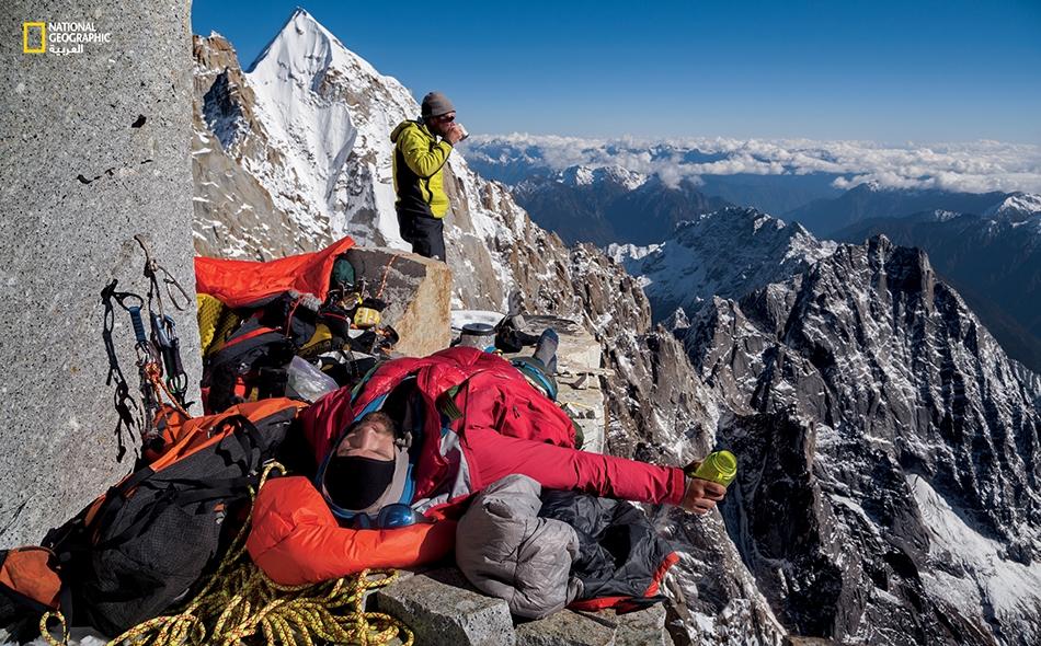مارك جنكينز ورنان أوزترك يستريحان خلال تناول الغداء في بقعة تطل على قمة كاكوبو رازي التي تغطيها الثلوج . كان المتسلقان يرغبان في أن يكونا أول من يتمكن من تحديد ارتفاع الجبل بكل دقة، باستخدام جهاز (GPS).