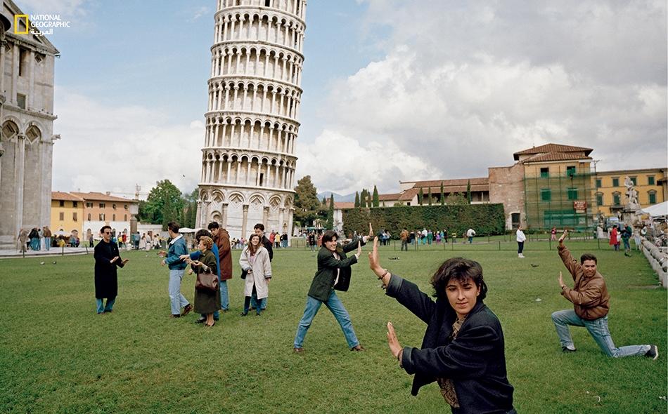 زوّار مرحون يتّخذون وضعيات تصوير وهم يميلون مع برج بيزا المائل. ظل هذا البرج الإيطالي يقاوم الجاذبية منذ 800 سنة ويزيد.