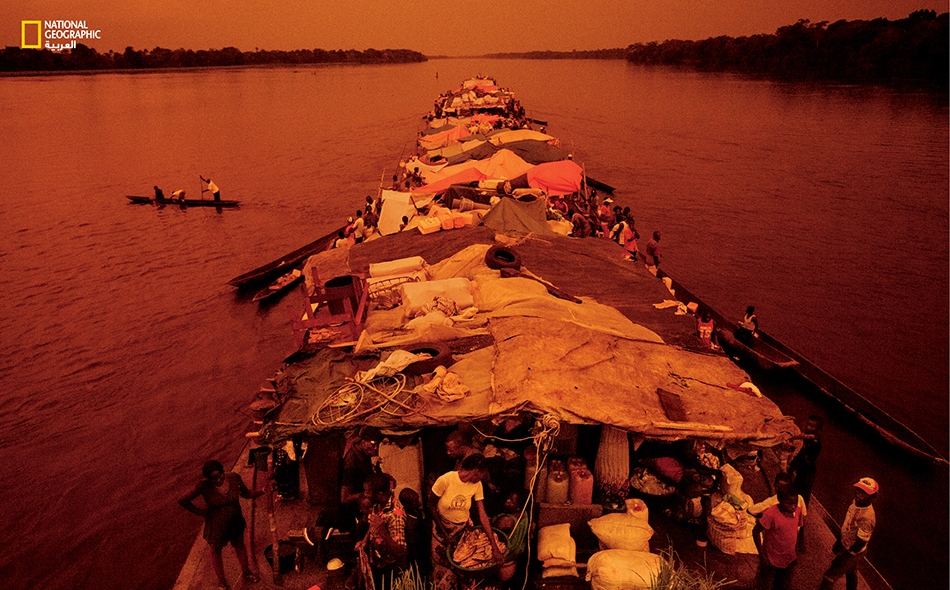 صندل (مركب نقل مسطح) مكتظّ بالركّاب يشق طريقه عبر مجرى نهر الكونغو وقد أفَلت الشمس في الأفق.