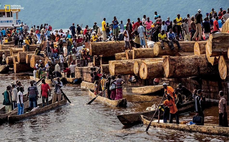 """في """"مالوكو"""" التابعة لمدينة كينشاسا، ينطلق بعض الركّاب من صندل محمّل بالأخشاب الكبيرة بطريقة عشوائية. تنتعش تجارة الخشب بصورة كبيرة على النهر، أما احتطابه فيعد أحد أسباب الانجراف الخطير للضفاف."""