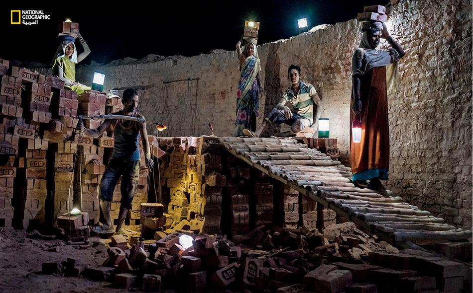 """داخل قمين لتصنيع القرميد في ولاية """"أوتار براديش"""" الهندية النائية، يستخدم العمال فوانيس تعمل بالطاقة الشمسية لتنير لهم مواضع أقدامهم. تجد دول العالم النامي معاناة في توفير الطاقة لشعوبها، إذ يفتقر قرابة 1.1 مليار نسمة حول العالم إلى الكهرباء."""
