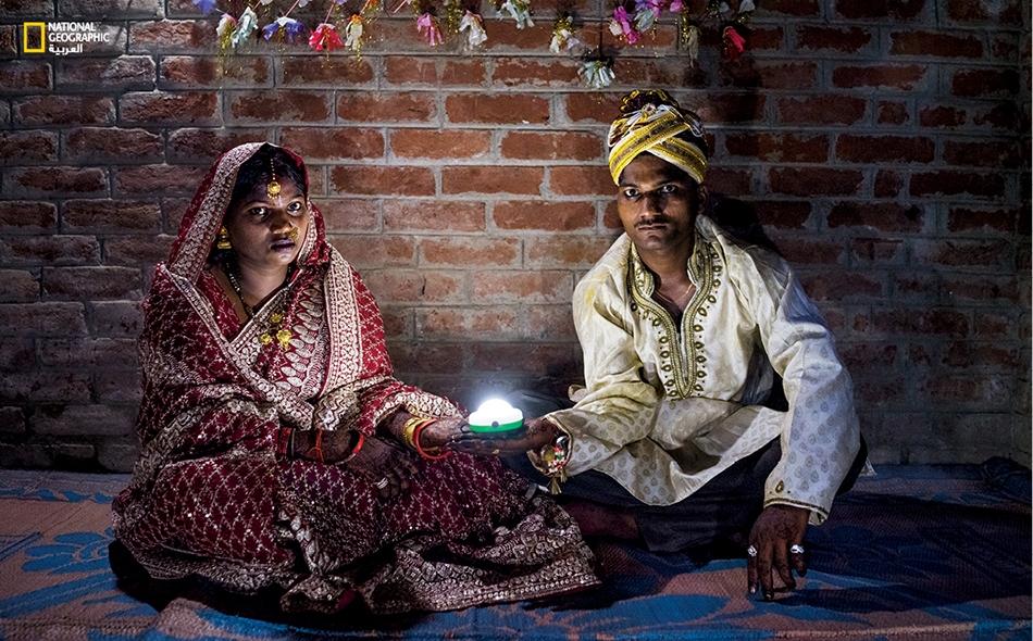 """تحتفل """"سوني سوريش"""" ذات العشرين ربيعاً مع """"سوريش كاشياب"""" (22 سنة) بزواجهما في ولاية أوتار براديش وهما يحملان مصباحا يعمل بالطاقة الشمسية؛ إذ تفتقر 20 مليون عائلة من سكان الولاية إلى الكهرباء."""