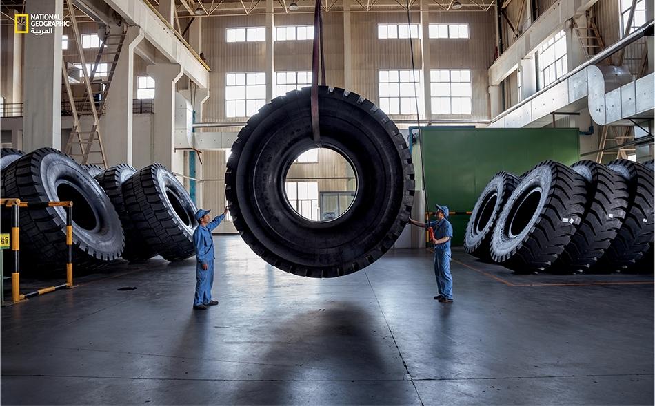 """عمال صينيون في شركة (Triangle Tyre) بمدينة """"ويهاي"""" ينقلون إطاراً يزن 3 أطنان ويُستخدم في المَركبات المنجمية."""