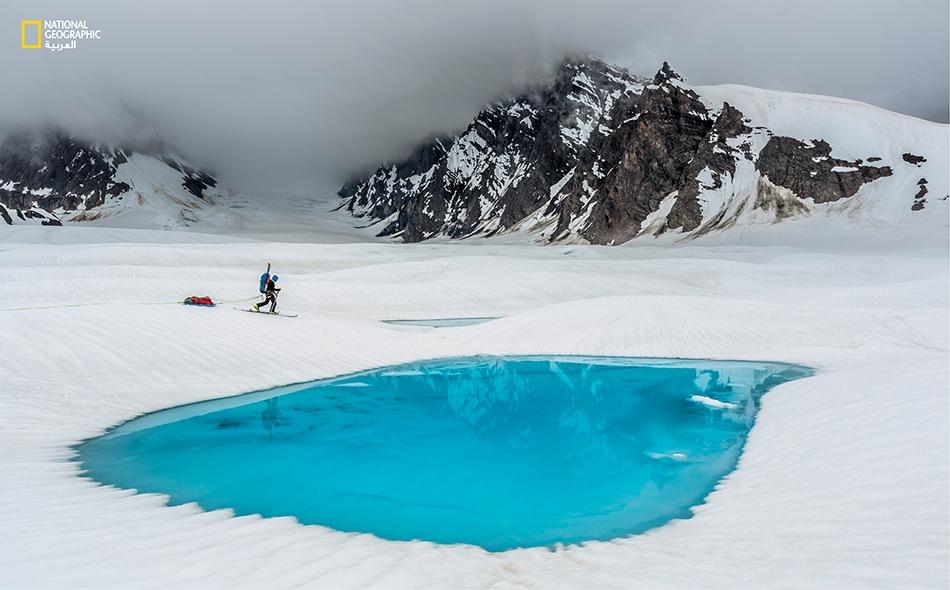 """ينسابُ أحد المتسلّقين بزلاّجتيه متجاوزاً بحيرةً بلون الياقوت الأزرق تعلو """"نهر روث الجليدي""""، إذ يتجّه نحو واحد من مئات سفوح الجبال التي لم تطأها قدم بشر في أصقاع منتزه دينالي القصيّة المهجورة."""