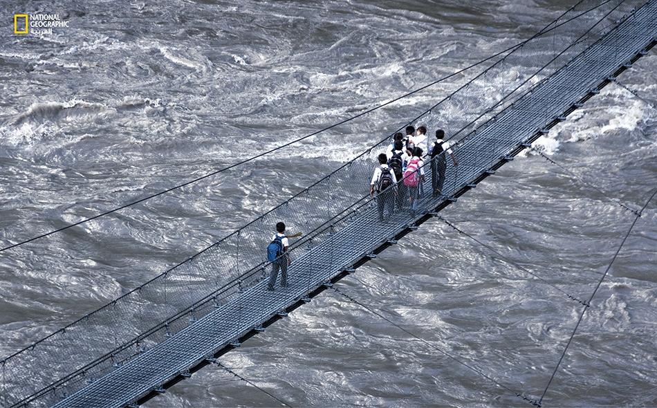 """أطفال في المرحلة الابتدائية يعبرون جسراً حديدياً مخصصاً للمشاة في بلدة """"شيتوان"""" وسط عصف شديد للرياح، فيما تتلاطم مياه نهر """"غاغارا"""" هادرةً أسفل منهم."""