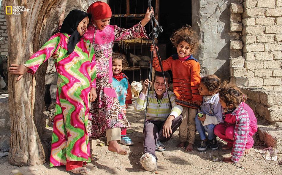 """""""مرجيحة"""" من قماش أسود أمام محل لبيع الدجاج -في قرية """"البرشا"""" بالظهير الصحراوي الشرقي لمدينة المنيا- تضفي شيئاً من البهجة على أطفال القرية."""