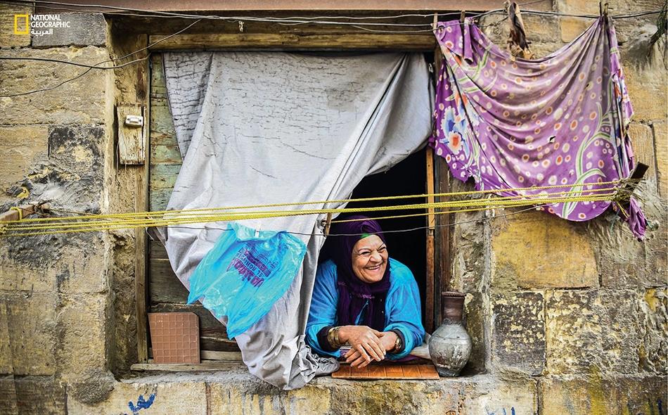 """""""أبلة حكمت"""" أو """"أم هويدا"""" كما يحلو لسكان حي """"الدرب الأحمر"""" بمصر القديمة مناداتها، تطل بابتسامتها من شباك منزلها."""