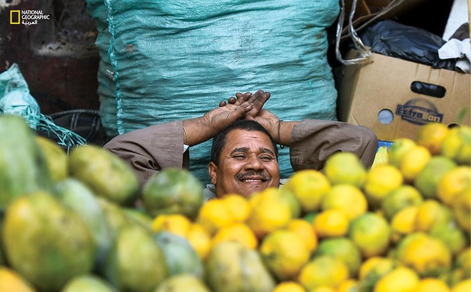 """في منطقة مثلث """"ماسبيرو"""" وسط القاهرة، يجلس بائع مانجا سعيداً خلف بضاعته."""