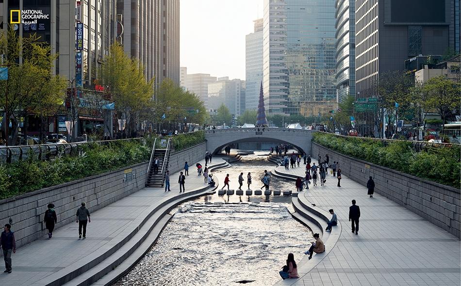 """يتلوّى """"تشونغيتشون"""" عبر مدينة سيؤول، عاصمة كوريا الجنوبية. ظل هذا الجدول مقبوراً تحت الأرض سنين طويلة، بعد أن كان شريان حياة المدينة. أما اليوم فقد كُشف غطاؤه فأصبح مكاناً يجتذب الأهالي وينعم فيه المرء بطبيعة المياه الملطّفة."""