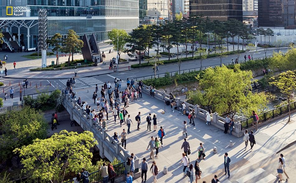 """""""تشونغيتشون"""" سيؤول، كوريا الجنوبية يصغي بعض المتنقّلين بين مساكنهم ومقرات عملهم إلى فرقة موسيقية على جسر للمشاة يصل بين جانبي المنتزه. على الرغم من أهمية النهر الصغير لثقافة المدينة ونموّها، فقد كان في ما مضى متقطّع الجريان، فيسيل في بعض الأوقات..."""