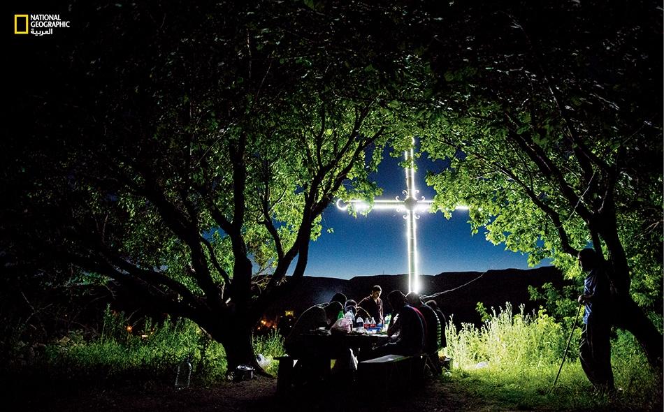 """يستريح أهالي قرية """"باغاران"""" الحدودية في أرمينيا، أثناء نزهة ليلية تحت أشجار المشمش، وقد شع صليب عملاق في تحدٍّ قبالة تركيا. إنهم يُغنّون بأصوات صارخة للذكرى والمكابدة الثقافية والنجاة."""