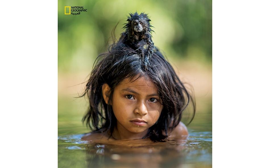"""يتشبّث قرد """"طمارين"""" مُستأنَس بالفتاة """"يوينا ماميريا نوتسوتيغا"""" التي تنتمي لقبيلة ماتسيغينكا، وهي تغمس نفسها في نهر """"يوميباتو"""" المتغلغل في أعماق منتزه مانو الوطني."""