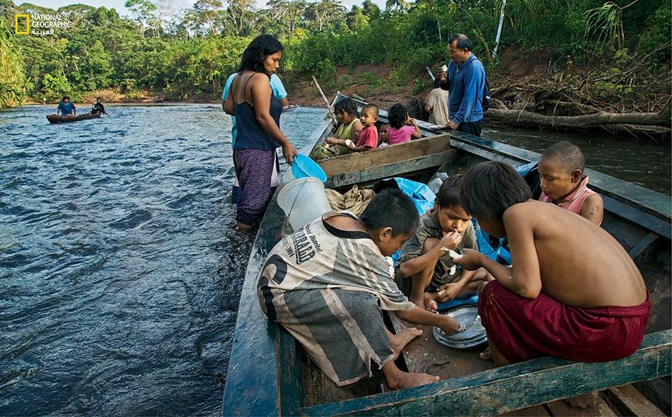 """أطفال مدارس من قبيلة ماتسيغينكا خلال رحلة ميدانية وهم يأكلون سمكاً صِيد بطريقة تقليدية: إذ تُهرَس جذور نبات """"البارباسكو"""" إلى أن تصبح عجينة ثم تُلقى بمياه النهر في حركة دوامية."""