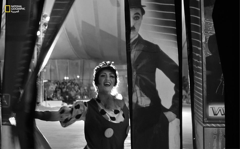 """المهرجة الروسية """"ناتاليا غونشاروفو"""" تزيح ستارة تحمل صورة أسطورة الكوميديا """"تشارلي تشابلن""""، قبيل دخولها الكواليس في أعقاب انتهائها من أداء فقرتها الكوميدية أمام الجمهور."""