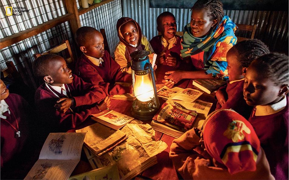 """على نور الشموع، تقضي كاكينيا نتائيا بعض الوقت مع طالبات لدى """"مركز كاكينيا للتميّز""""."""