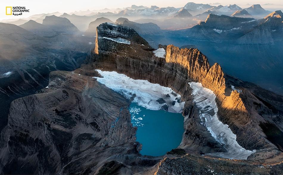 """تلقي شمس الصباح الباكر بأشعتها على """"غاردن وَول"""" (أي """"جدار الحديقة"""")، وهو نتوء صخري شكّلته أنهار جليدية تعود إلى العصر الجليدي. وقد كان نهر """"غرينل"""" الجليدي فيما مضى يملأ الحوض الواقع أسفل الجدار، لكنه يتقلّص."""