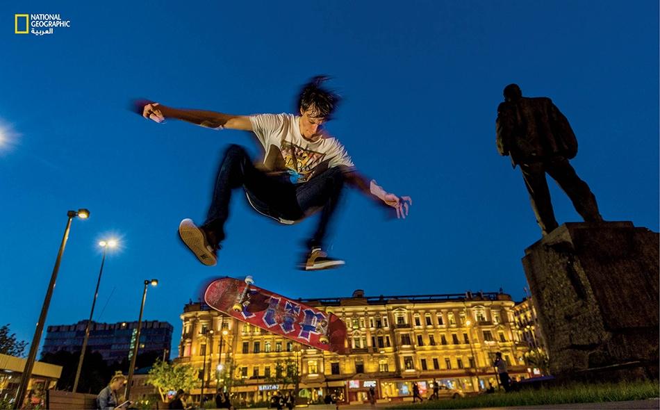 """""""ميخائيل فاسيليف"""" بائع معدات بلياردو في التاسعة والعشرين من عمره، يتمرن على حركات لوح التزلج في """"ساحة تريومفالنايا"""" في موسكو قريبا من تمثال """"فلاديمير ماياكوفسكي""""، الشاعر الذي تغنى بأمجاد الثورة البلشفية لعام 1917."""