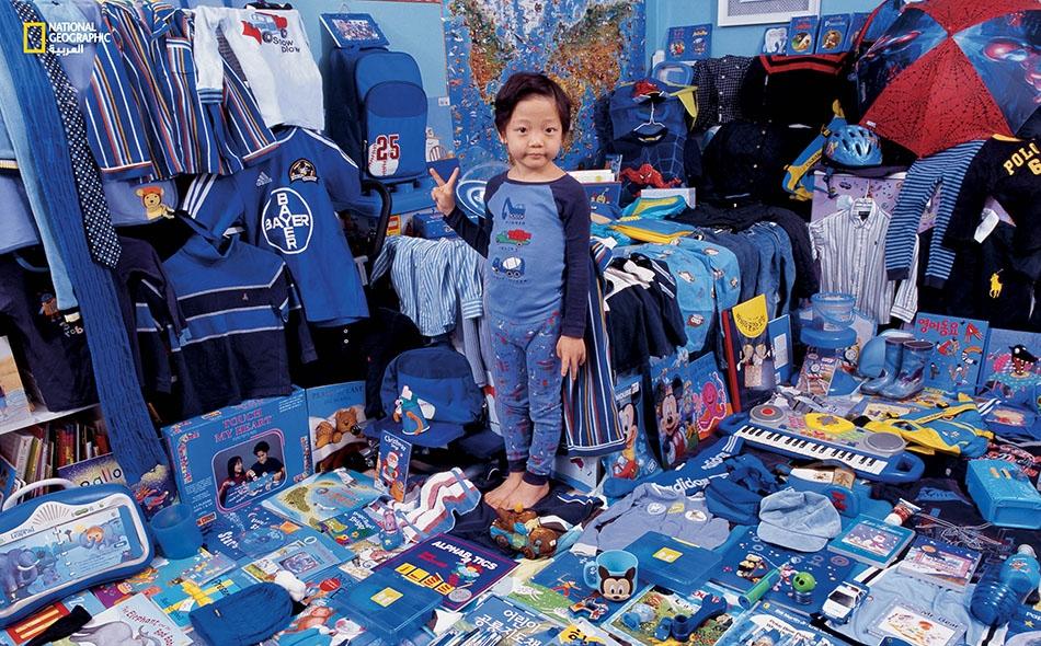 """""""دونغهو"""" (6 أعوام)، في هذه الصورة الملتقَطة عام 2008، وسط ألعابه وثيابه وكتبه وغيرها من أغراضه الزرقاء."""