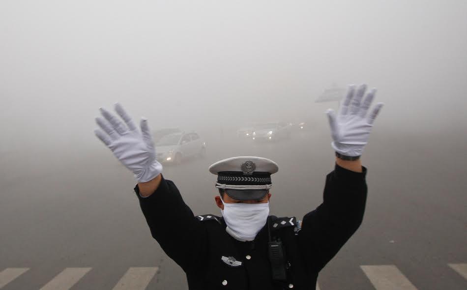 شرطي ينظم حركة مرور السيارات في إحدى التقاطعات الرئيسة في بكين.