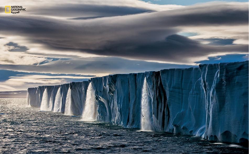 """ينساب الماء دافقاً عقب ذوبان الجليد في جزيرة """"نورد أوسلايت"""" بأرخبيل """"سفالبارد"""" بالنرويج. ترتفع درجة حرارة القطب الشمالي بوتيرة أسرع من أي مكان آخر على سطح الأرض؛ ويقول العلماء إن جليد البحر الصيفي ربما يصبح أثراً بعد في هذه المنطقة إذا استمرت هذه..."""
