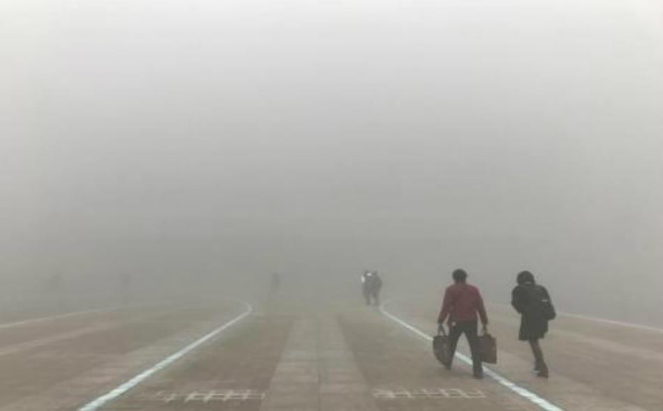 أشخاص يسيرون وسط ضباب دخاني في إقليم هينان الصيني يوم 9 يناير 2017.