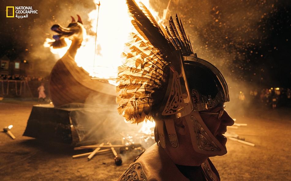 """يحتفل أحد أبناء جزر """"شتلاند"""" بتراث أجداده الفايكينغ، مُرتدياً خوذته المريّشة التي هي أقرب إلى الخيال منها إلى الواقع، لدى مهرجان """"أب هيلي آ"""" (Up Helly Aa) الناري السنوي."""