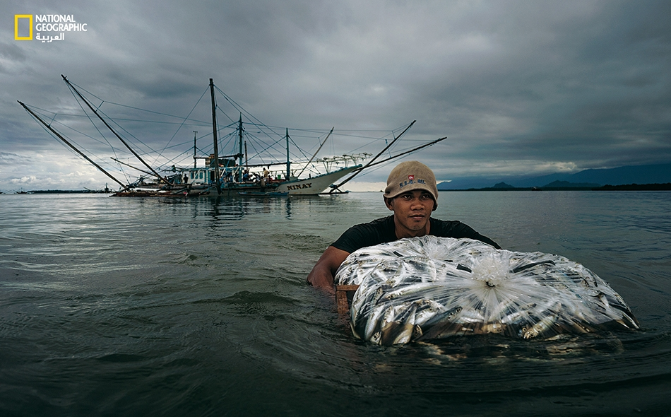 صياد فلبيني يشق طريقه وسط الماء باتجاه الشط، حاملاً معه نصيباً مما اصطاده فريقه.