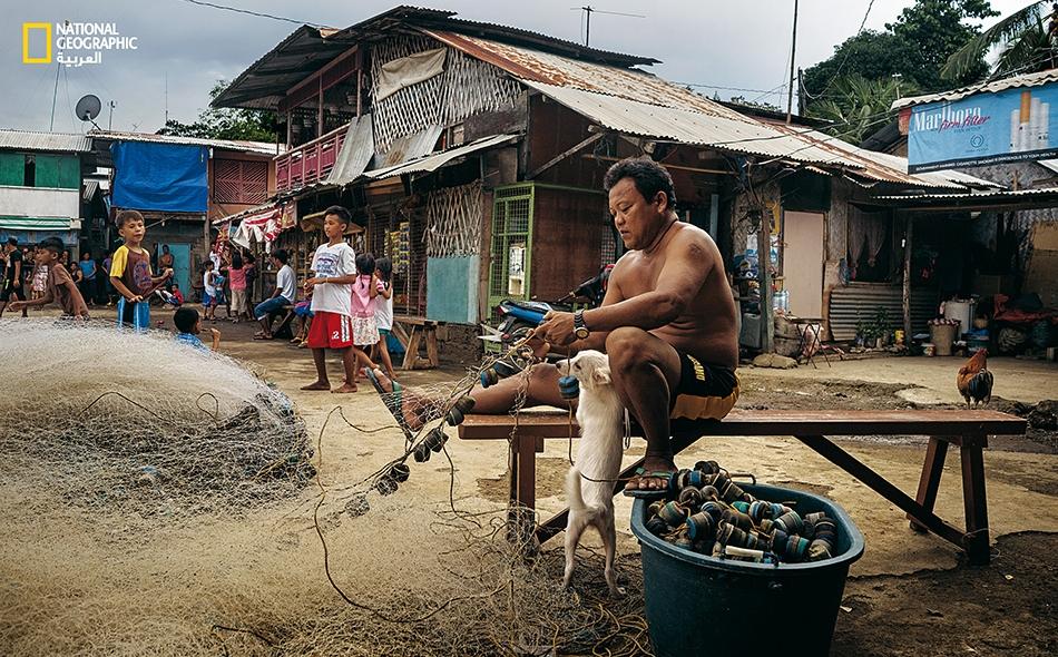 """رجل فلبيني يصلح شباكه في قرية للصيادين بمدينة """"بويرتو برنسيسا""""."""