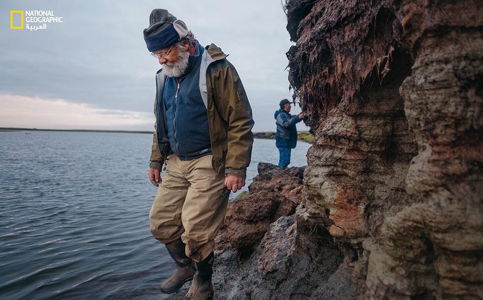"""يقوم عالم الآثار """"ريك كنيكت"""" (يسار) والزعيم المحلي """"وارن جونز"""" باستكشاف المناطق المتاخمة لنهر """"أروليك""""، بعدما اكتشفت معلمة محلية قوس صياد بارزاً من ضفة النهر المتآكلة."""