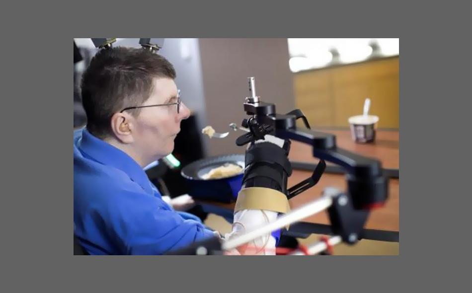 """يستخدم """"بيل كوتشيفار"""" تقنية أنظمة كمبيوتر تحاكي الدماغ وجهاز التحفيز الكهربي لتحريك ذراعه بعد ثمانية أعوام من الشلل."""