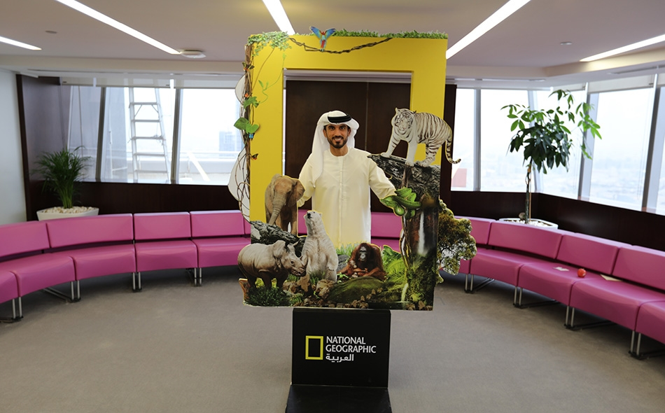 أحد موظفي شركة دو في لقطة تذكارية بجانب الإطار الخاص بناشيونال جيوغرافيك العربية.