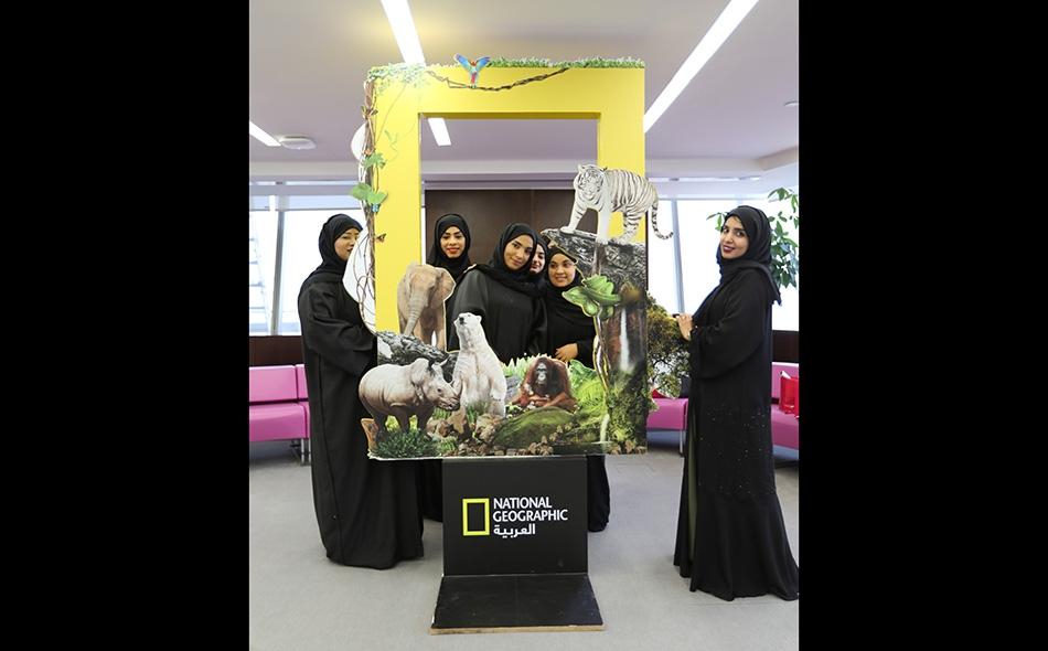 مجموعة من موظفي شركة دو أثناء التقاطهم صورة تذكارية بجانب الإطار الخاص بناشيونال جيوغرافيك العربية.