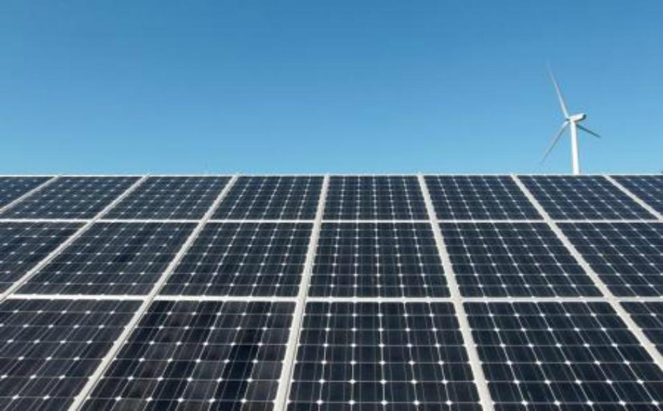 توربين لتوليد الطاقة من الرياح خلف ألواح شمسية في إنتشون بكوريا الجنوبية.