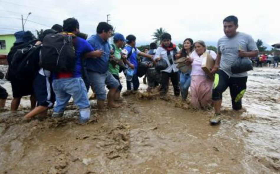 """سكان يعبرون شارعا غمرته مياه الفيضانات في """"تروجيلو"""" شمال البيرو. صورة: دوجلاس جوريز."""