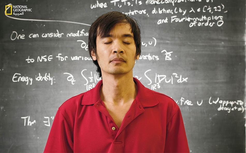 """يقف خبير الرياضيات """"تيرانس تاو"""" أمام سبورة كتب عليها صيغهُ عن ديناميكا السوائل. لقِيتْ """"براعته الفريدة"""" الترحاب، ومُنح """"ميدالية فيلدز"""" عام 2006 في سن الحادية والثلاثين."""