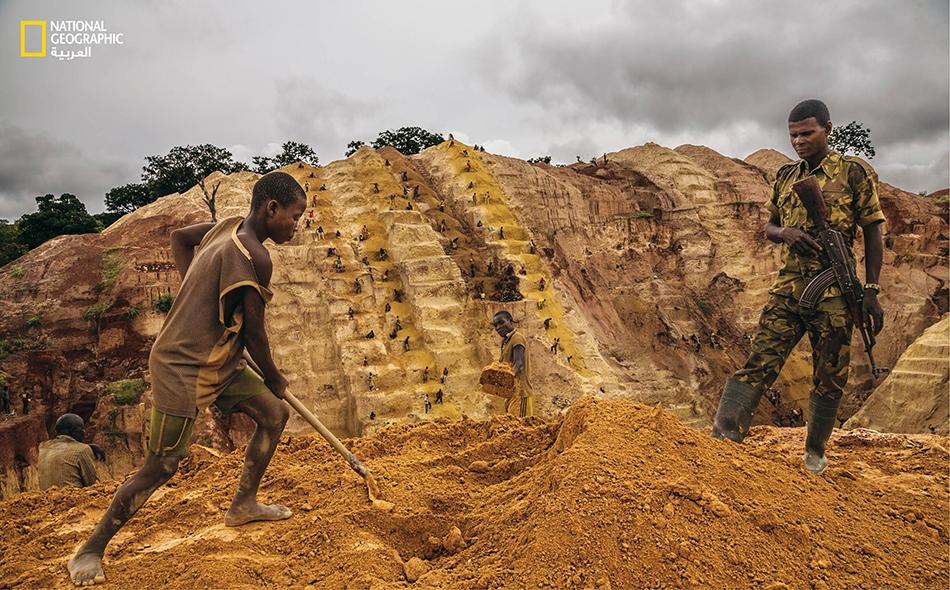 """متمردٌ مسلم يقف ببندقيته الرشاشة لحراسة الرجال والفتيان العاملين في حفر منجم للذهب يقع في ضاحية مدينة """"بامباري"""". يحصل هؤلاء المتمردون على حصة من الذهب لقاء توفير """"الأمن""""."""