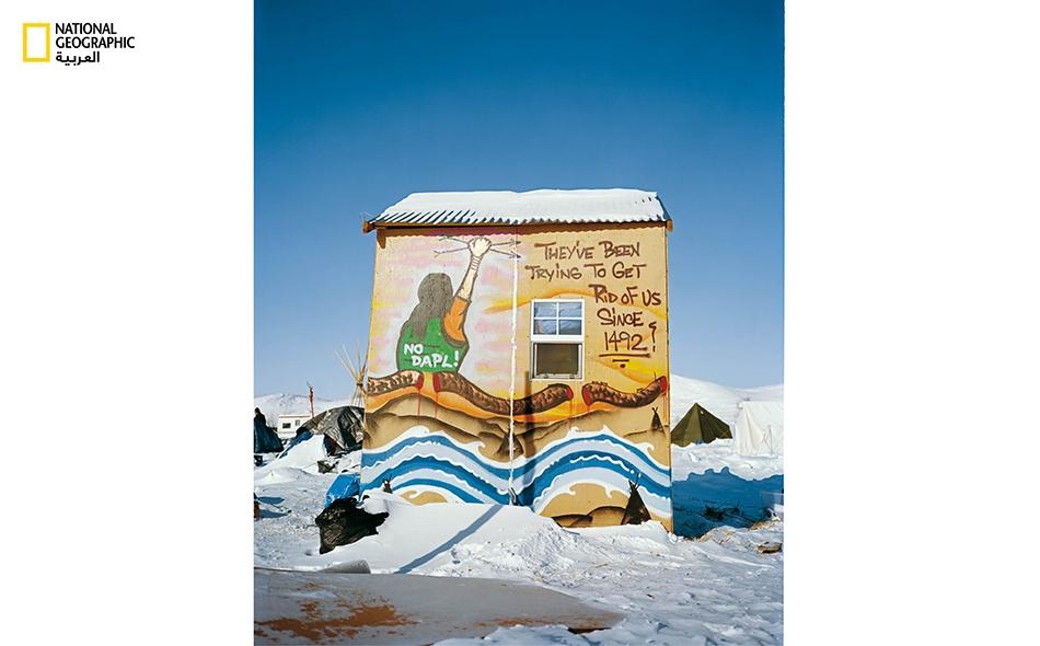 """رسم في المخيم يظهر أفعى سوداء اللون ـرمز أنبوب النفطـ قُطعت على يد أحد """"حماة الماء""""."""