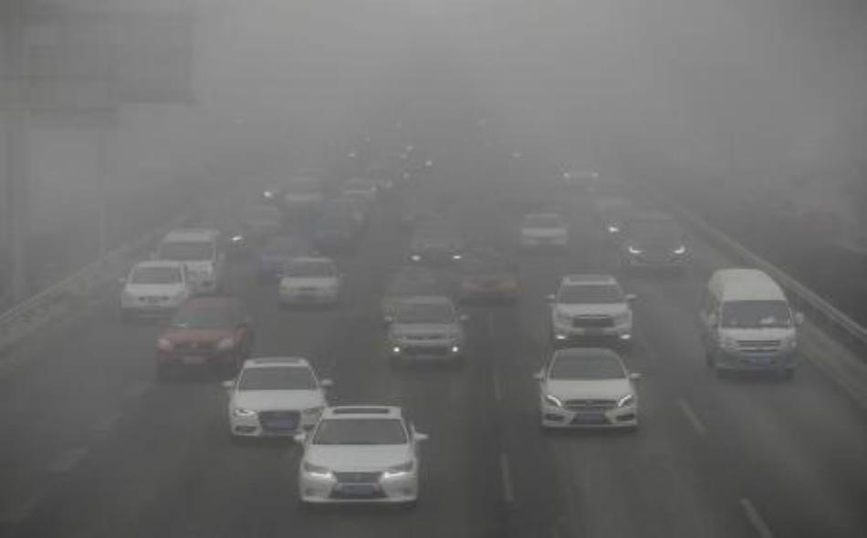 سيارات وحافلات تسير وسط ضباب دخاني في طريق رئيس بالعاصمة بكين يوم 14 فبراير 2017. تصوير: جاسون لي.