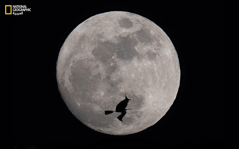 """لتجسيد هذا المشهد الخرافي، طلب المصور -بعد تحديد مسار القمر- إلى أحد زملائه القيام بحركات بهلوانية على """"بساط قفز""""، غير ظاهر في الصورة، بعد ارتدائه قبعة السحرة الشهيرة مستعيناً بمكنسة ذات رقبة طويلة."""