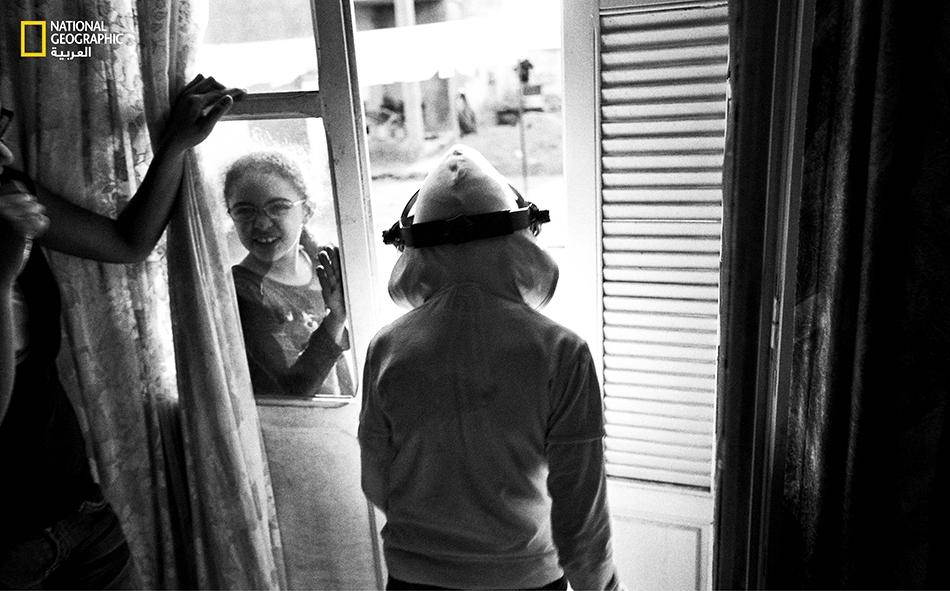 """تهمُّ أماني (عشر سنوات) المصابة بمرض """"جفاف الجلد المصطبغ"""" بالخروج لمدة زمنية محدودة للعب مع شقيقاتها غير المصابات، مرتدية قناعاً واقياً وقفازين."""