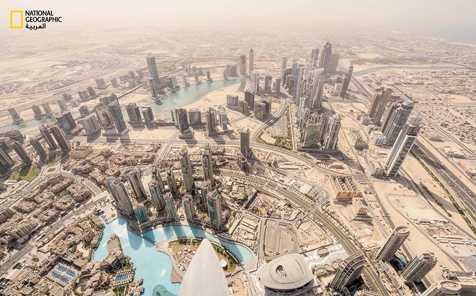 يتدفق السائحون على برج خليفة -أعلى ناطحة سحاب في العالم بارتفاع يصل إلى 828 متراً- للاستمتاع بإطلالة عين الطائر هذه. تميل بعض المخططات العمرانية الجاري تنفيذها حالياً إلى الارتفاعات الأقل؛ مثل دار الأوبرا (أسفل المنتصف) التي تشكل جزءاً من حي جديد،...
