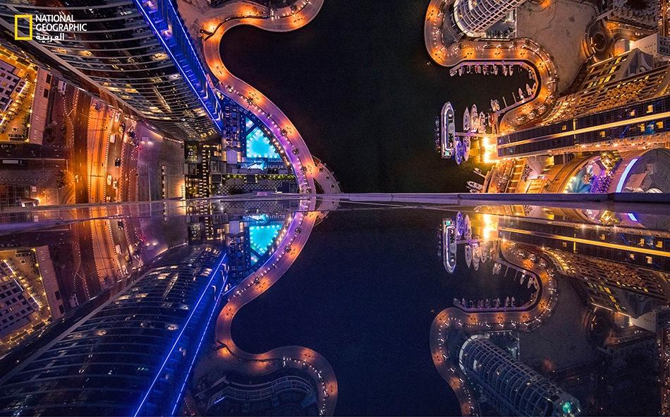 """من علو 180 مترا أسفل برج """"باي سنترال""""، يظهر """"مرسى دبي"""" بيخوته فيما تتلألأ أضواء ممشى """"مارينا دبي"""" مثل قناديل من لؤلؤ الخليج."""