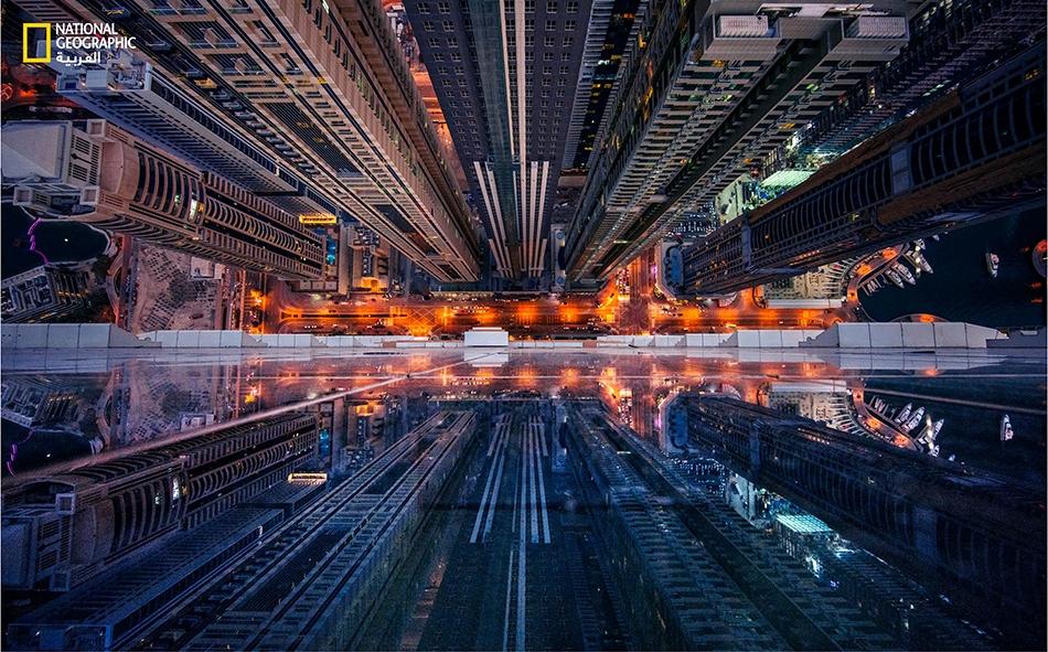 """مثل قعر وادٍ سحيق، يظهر """"شارع المارينا"""" بدبي في وسط الصورة، فيما تنعكس الأضواء وصور المباني المحيطة فوق الواجهة الزجاجية لبرج """"إيليت تاور"""" بطوابقه التسعين."""